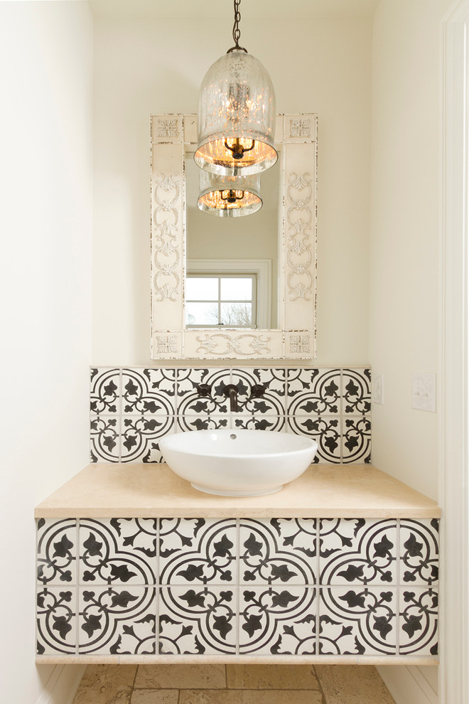 un'antica lampada a sospensione in vetro, una vanità incorporata rivestita con piastrelle marocchine bianche e nere e un lavandino (wb builders)