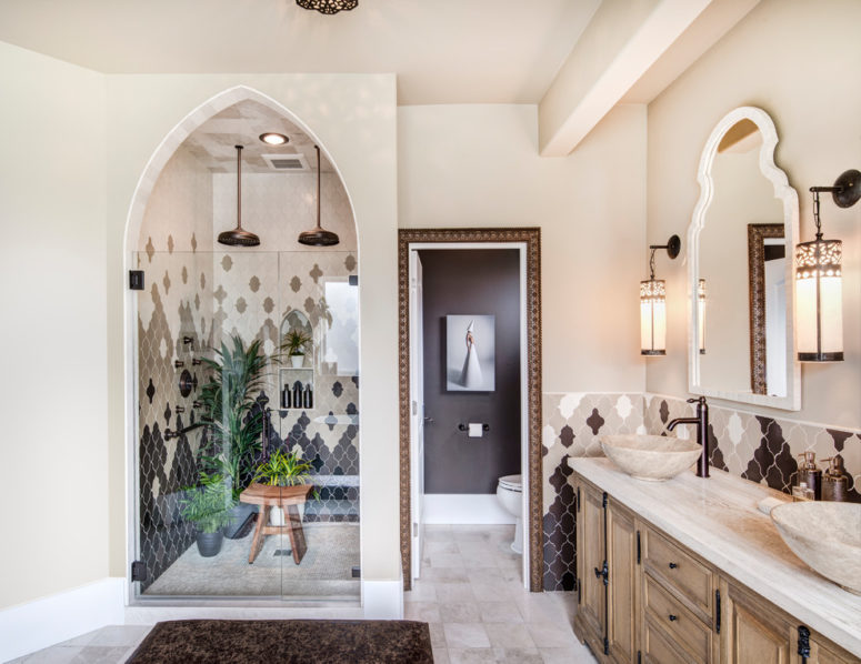 un bagno padronale marocchino include un mobile da toeletta in legno intagliato a mano realizzato in Marocco e piastrelle marocchine bianche e nere disposte in modo accattivante (costruzione Harjo)