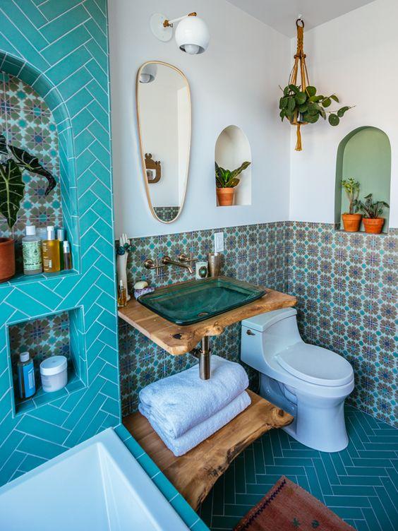 un bagno di ispirazione marocchina con piastrelle colorate, nicchie per la conservazione, vegetazione in vaso e un lavandino in vetro turchese