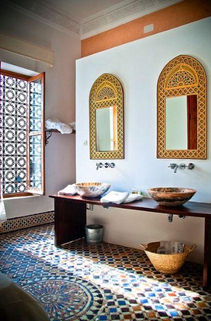 un colorato bagno marocchino con specchi orientati, lavandini dipinti, un pavimento piastrellato e una bella finestra