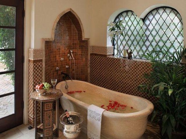un bagno marocchino con piastrelle accattivanti, una nicchia a forma di orientale, una vasca da bagno in pietra, un tavolino intagliato e una vegetazione in vaso