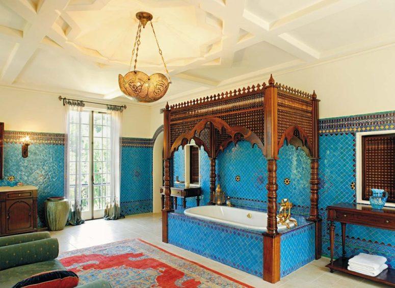 un audace bagno marocchino blu con una lampada a sospensione, una vasca da bagno con una struttura in legno sulla parte superiore e un tappeto luminoso e vasi (Chris Barrett Design)