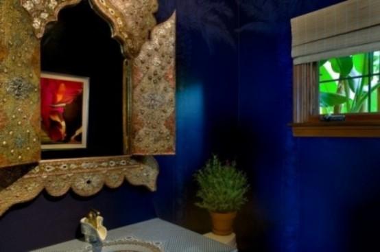 un bagno blu brillante con uno specchio decorato, piante in vaso e sfumature romane