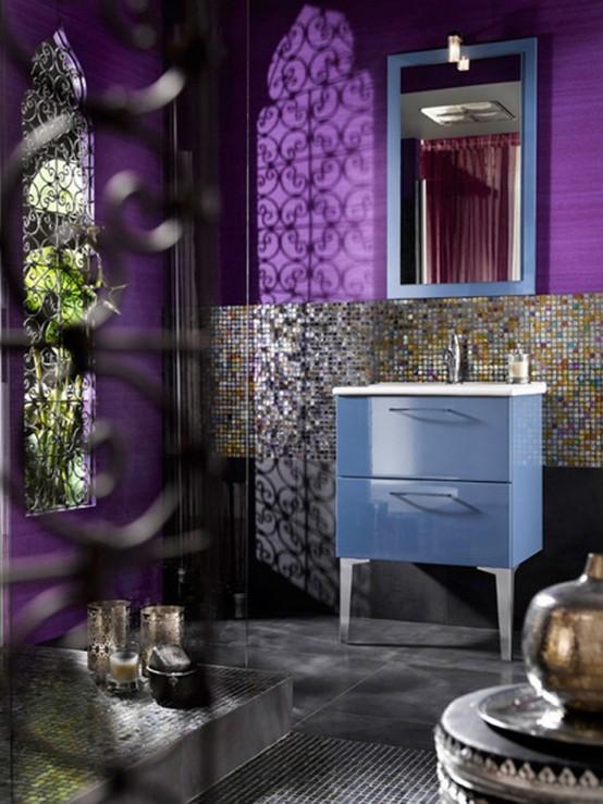 un bagno marocchino super colorato con pareti viola, piastrelle accattivanti, una vanità blu e uno specchio con cornice blu