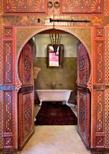 un bagno marocchino super colorato con pareti a motivi rossi e blu, una lanterna marocchina, pareti verdi e un tappeto boho