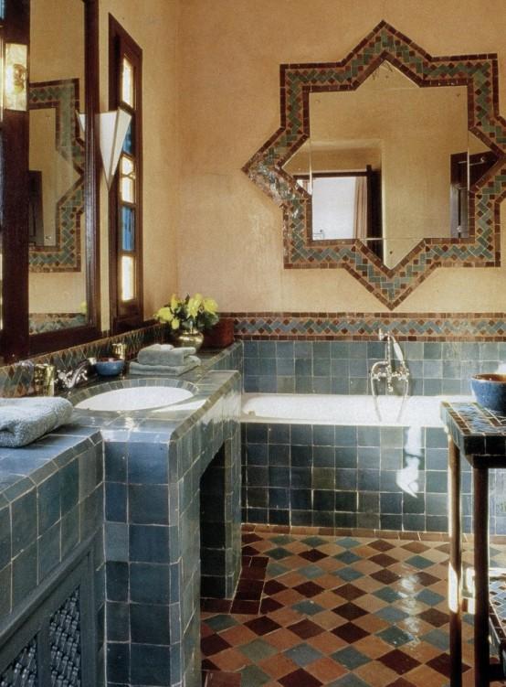 un colorato bagno marocchino con un pavimento in piastrelle a mosaico, vanità in piastrelle blu, uno specchio a forma di stella