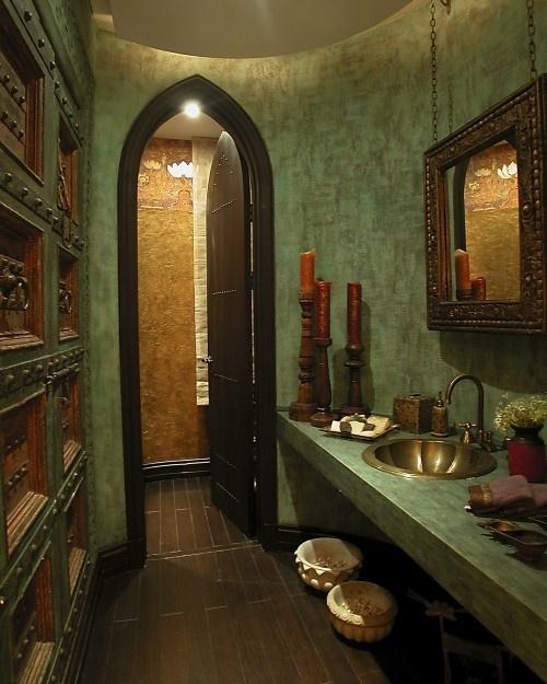 un bagno marocchino verde con un lavandino in ottone, uno specchio decorato, una parete con ante e maniglie in metallo