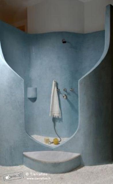 un bagno in gesso blu con uno spazio doccia intagliato e un pavimento di cemento