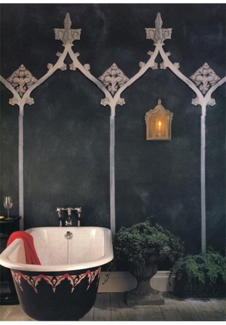 un bagno marocchino scuro con pareti nere con motivi, piante in vaso e una vasca da bagno decorata