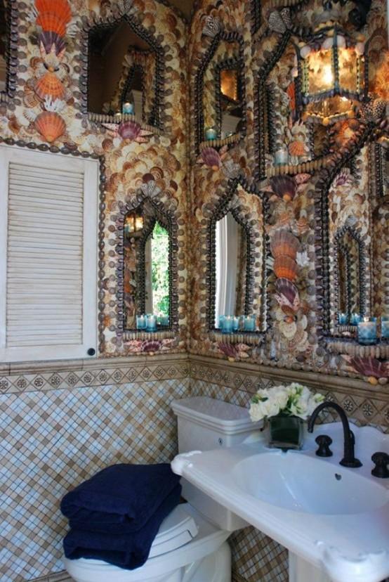 un bagno da spiaggia accattivante con pareti rivestite di conchiglie di mare, specchi decorati, piastrelle e una persiana per l'arredamento