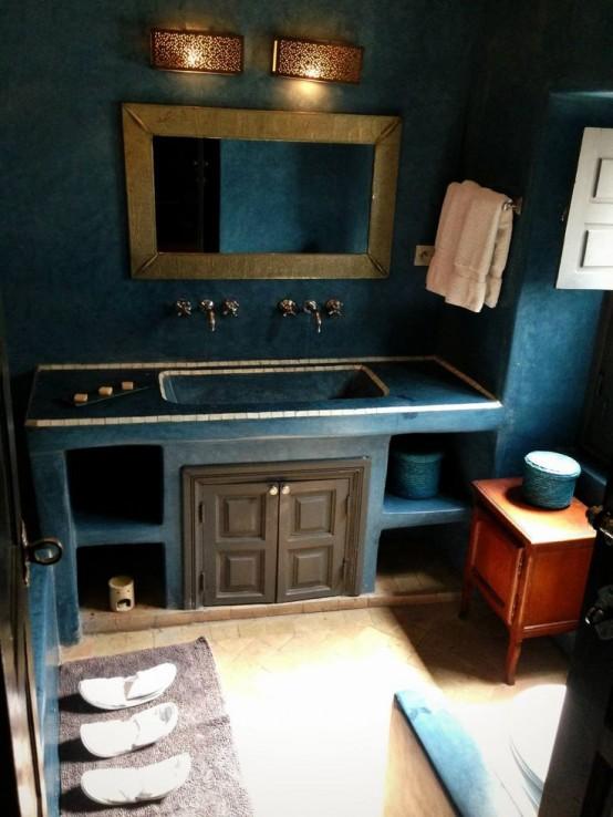 un bagno marocchino blu scuro con una vanità incorporata, uno specchio con cornice dorata, lampade da parete e una credenza in legno