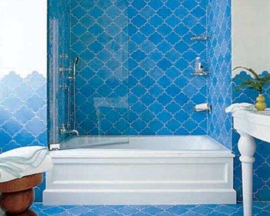 un bagno blu brillante con piastrelle marocchine e mobili di ispirazione vintage