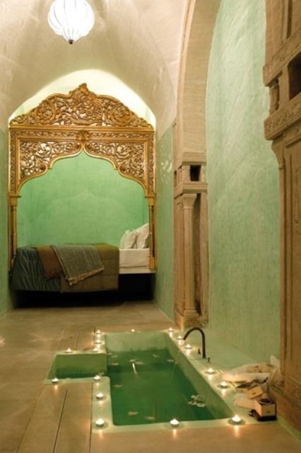 un bagno grene situato in una camera da letto, con una vasca incassata con candele e un rubinetto più pilastri incassati nelle pareti