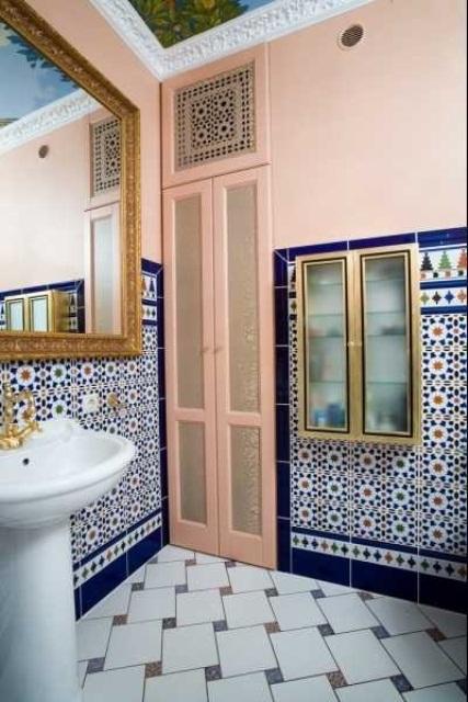 un bagno rosa con piastrelle blu scuro e bianche sulle pareti e sul pavimento, con uno specchio con cornice dorata e un rubinetto in ottone