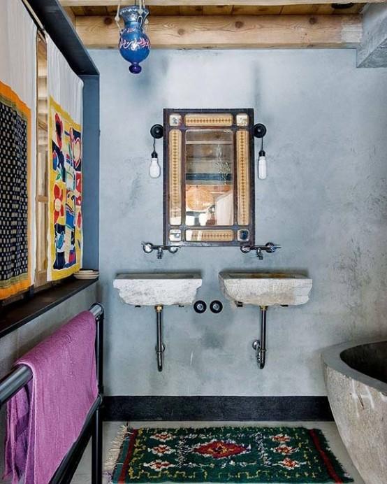 pareti in gesso blu, una vasca da bagno in cemento, tappeti e tende stampati e lavandini in cemento