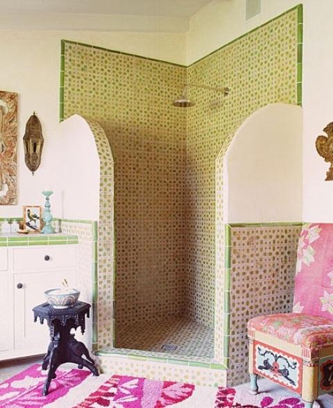 un bagno marocchino con piastrelle a motivi geometrici verdi, lampade da parete, un tappeto rosa e una sedia