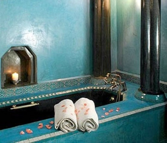un bagno turchese con una vasca rivestita di piastrelle più una nicchia con una candela
