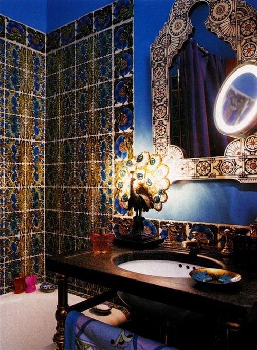 un colorato bagno marocchino con piastrelle luminose, uno specchio decorato, una bella lampada da tavolo a forma di pavone