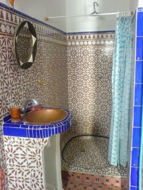 un bagno marocchino fatto con piastrelle a motivi geometrici, tocchi di viola, un lavandino in ottone e uno specchio decorato