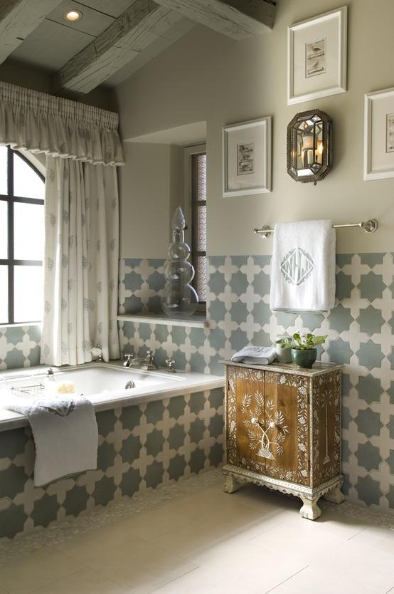 uno spazio neutro con piastrelle marocchine grigie e bianche, una credenza in legno dipinto e alcune opere d'arte