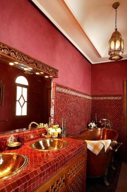 un bagno bordeaux fatto di gesso e piastrelle, con un lavabo piastrellato, una lampada a sospensione e una cornice dello specchio in legno intagliato