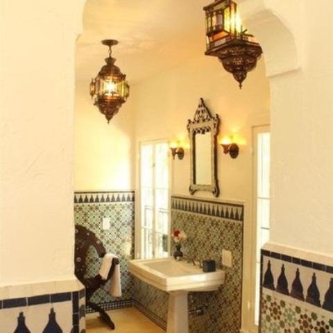 un bagno neutro con piastrelle a mosaico, lanterne marocchine e uno specchio accattivante in una cornice di legno
