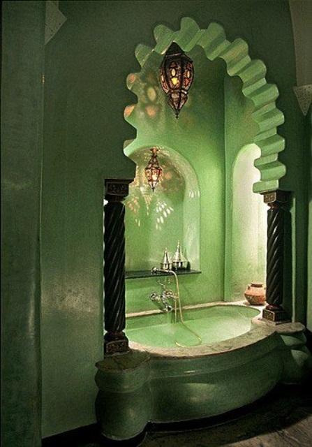 un bagno marocchino grigio con una vasca rivestita in pietra con pilastri e un arco scolpito più lanterne marocchine