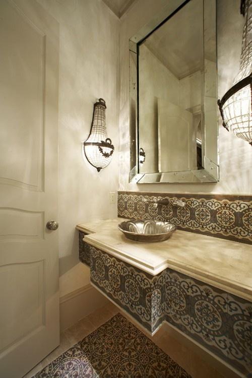 un bagno neutro rivestito con piastrelle marocchine sul pavimento e sulla vanità e lampade chic