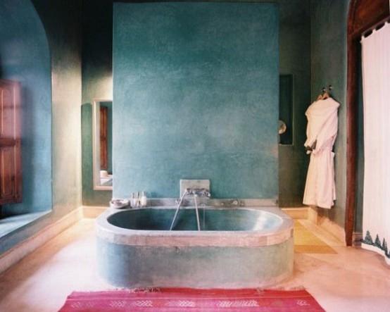 un bagno in gesso blu con una vasca da bagno in cemento, persiane in legno e un tappeto rosa