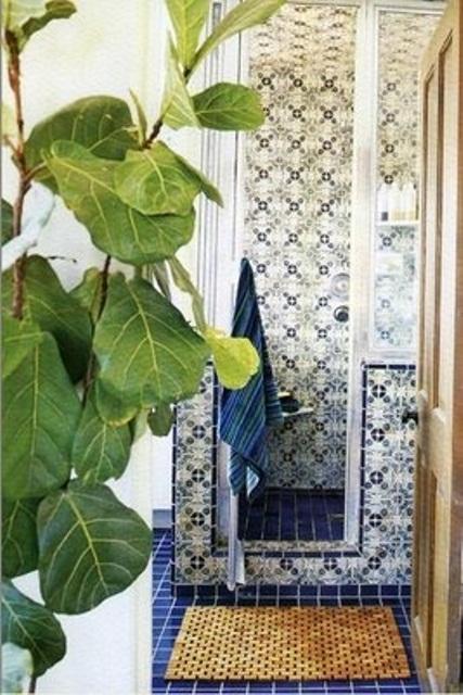 un bagno marocchino blu scuro e bianco con piastrelle a motivi geometrici accattivanti e vegetazione in vaso