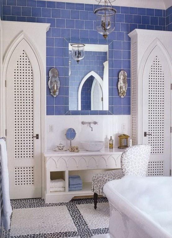 un bagno viola e bianco con porte ad arco, un pavimento di piastrelle di ciottoli, una vanità intagliata e una lampada di vetro