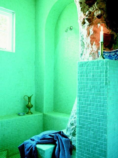 un bagno turchese e verde brillante con candele e una brocca di metallo vintage
