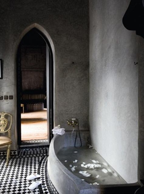 un bagno marocchino con pareti di cemento e una vasca in cemento, piastrelle bianche e nere e una porta ad arco