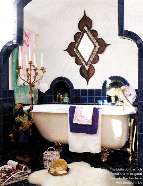 un bagno piastrellato blu scuro e bianco con uno specchio decorato, un bellissimo portacandele e un tappeto in pelliccia sintetica