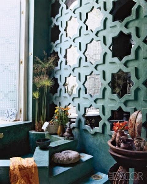 un bagno rivestito di gesso fatto in turchese, con una parete a specchio fatta con cornici a forma di stella e fiori in vaso