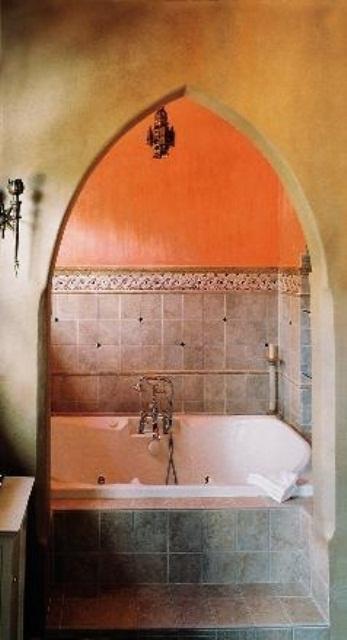un colorato bagno marocchino fatto in beige sabbia e arancione con una vasca rivestita di piastrelle