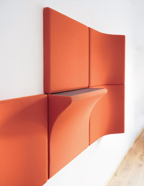 pannelli acustici arancioni audaci e un pannello con un ripiano aggiuntivo è un'idea molto funzionale