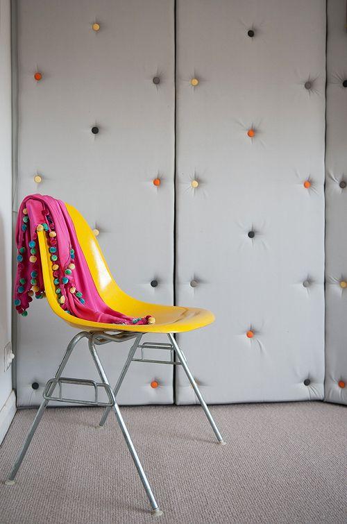 pareti grigie imbottite con chiodi decorativi colorati rendono lo spazio ultra moderno e giocoso