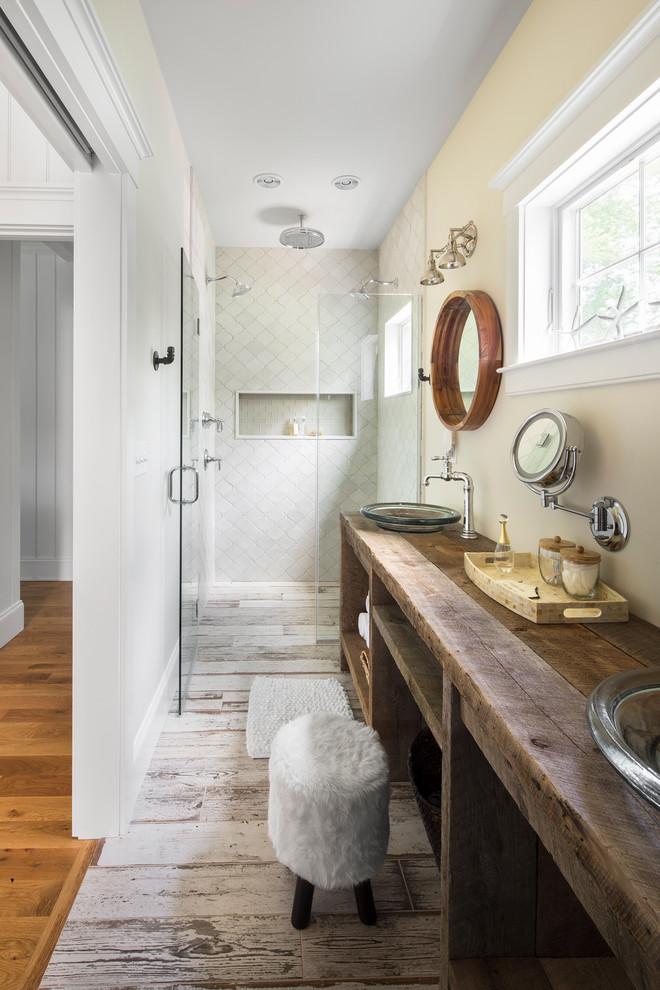 un accogliente rustico incontra un bagno contemporaneo con un grande lavabo, un pavimento in legno imbiancato e uno specchio rotondo (GMT Home Designs Inc.)