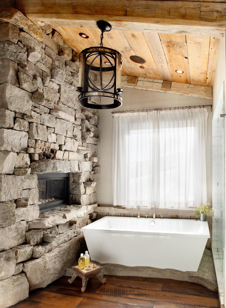 un accogliente bagno con parete in pietra naturale, soffitto e pavimento in legno e una comoda vasca (Peace Design)
