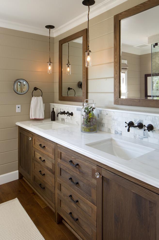 un bagno rustico incontra il moderno con una grande vanità in legno con un piano di lavoro bianco e specchi abbinati (Anne Sneed Architectural Interiors)