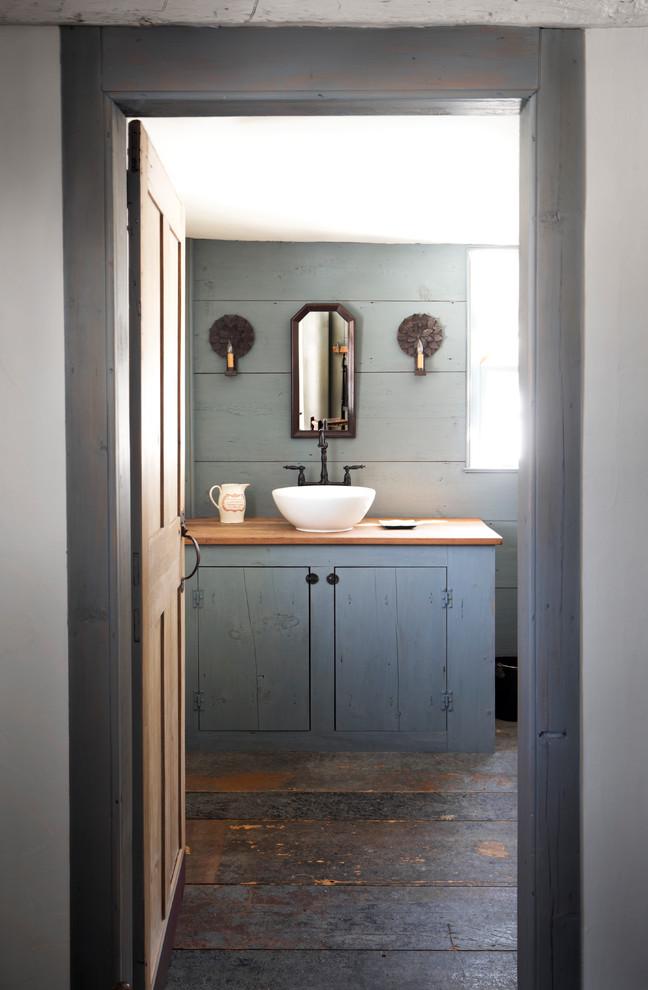 un bagno grigio ardesia con un pavimento in legno esposto alle intemperie e una vanità in grigio e un muro grigio (Fotografia di Tim Lenz)