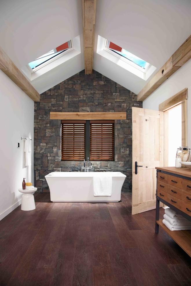 un bagno rustico contemporaneo con un pavimento in legno e un muro di pietra, un lavabo in legno (Skylight Specialists, Inc.)