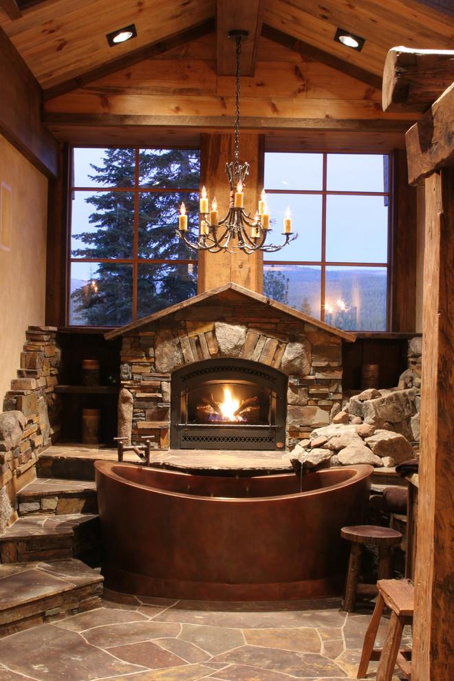 uno splendido bagno da chalet con molta pietra naturale e legno, con una grande vasca in metallo (High Camp Home)