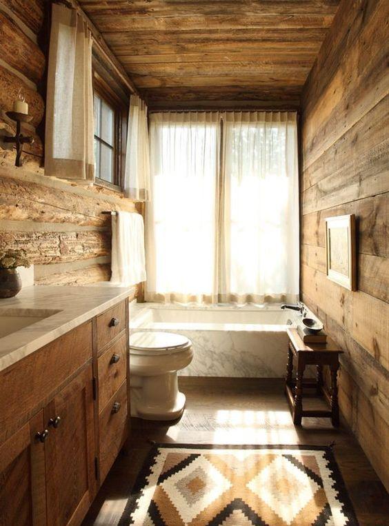 un accogliente bagno rustico fatto con molto legno e una vasca rivestita in marmo per un'atmosfera accogliente