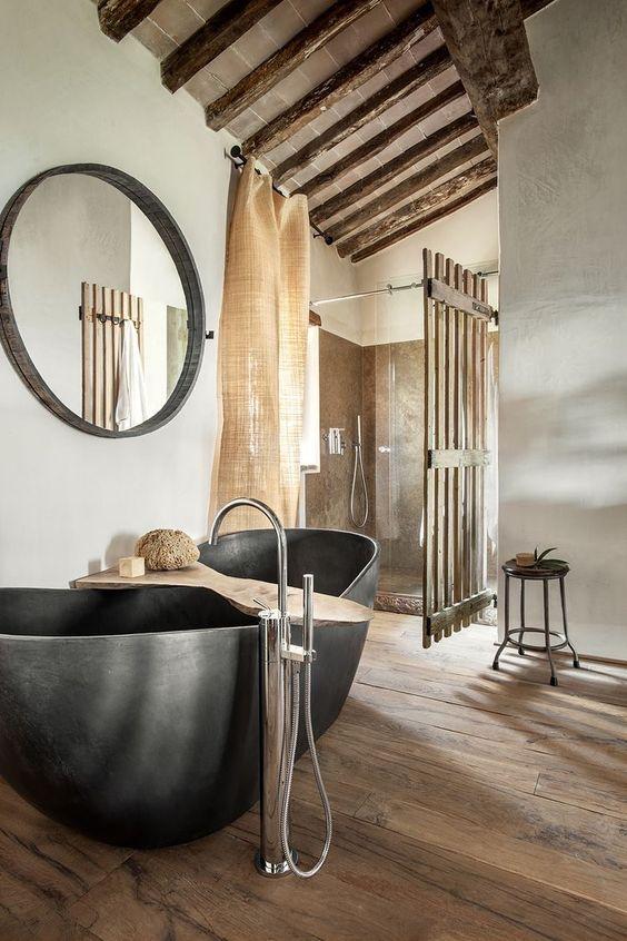un moderno incontra il bagno industriale con una vasca in pietra, tende di juta e molto legno