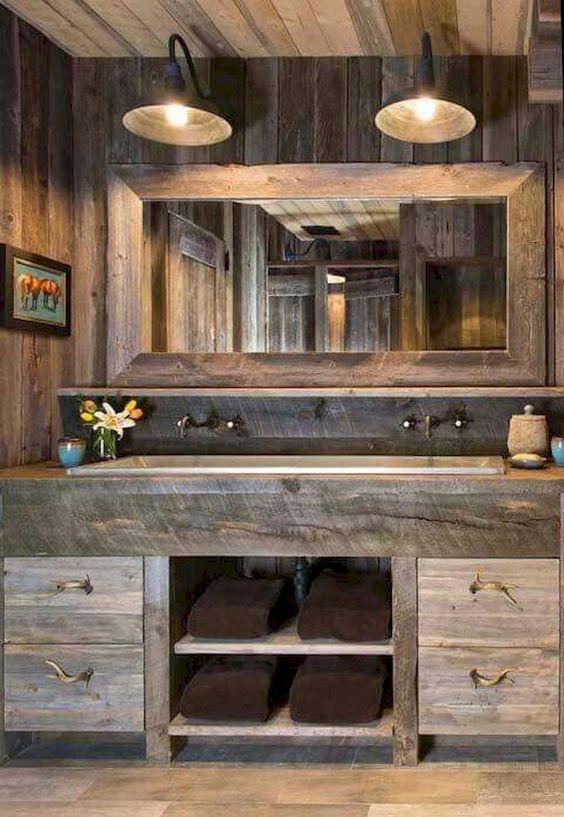 un bagno da fattoria in legno stagionato, con un grande specchio e lampade da parete