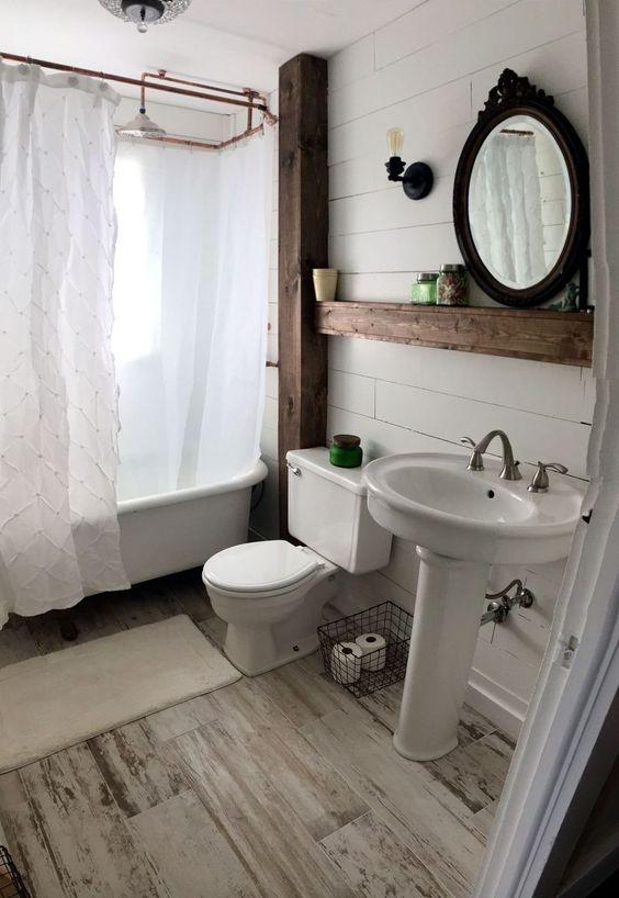 un bagno da fattoria con pareti in assi di legno imbiancate e un pavimento, tocchi di rame e oggetti vintage