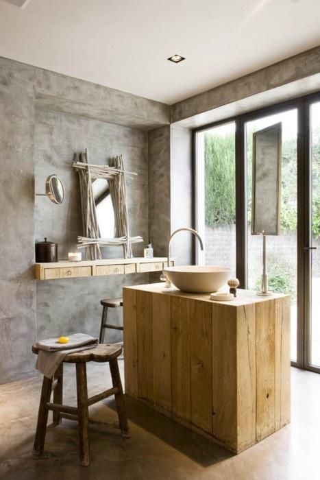 un bagno minimalista di cemento e legno di colore chiaro, il legno dona un'atmosfera accogliente