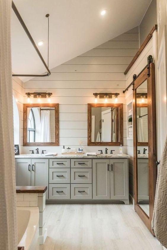un moderno bagno da fattoria con vanità di colore chiaro, specchi con cornice in legno e pavimenti e pareti imbiancati